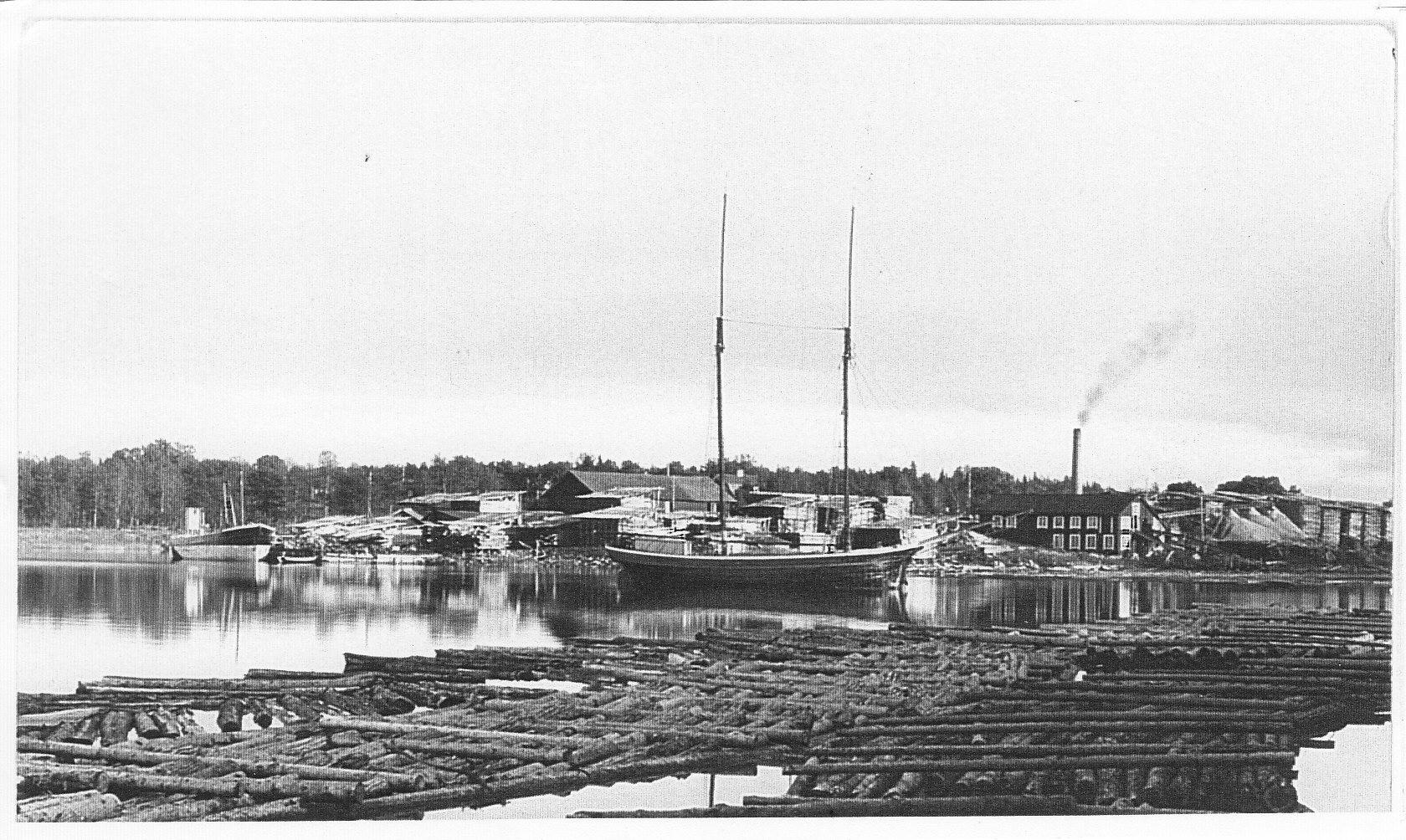 """Bogserbåten """"Emil"""" som tillhörde Elmsta Ångsåg. Vid sågens brygga ligger skutan """"Sari""""."""